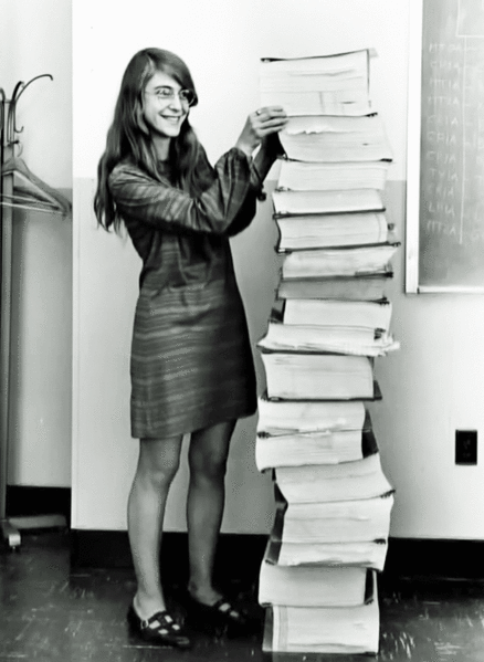 Photo of Margaret Hamilton standing next to the code she wrote for NASA's Apollo program.